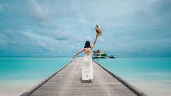海にかかる橋に立つ女性