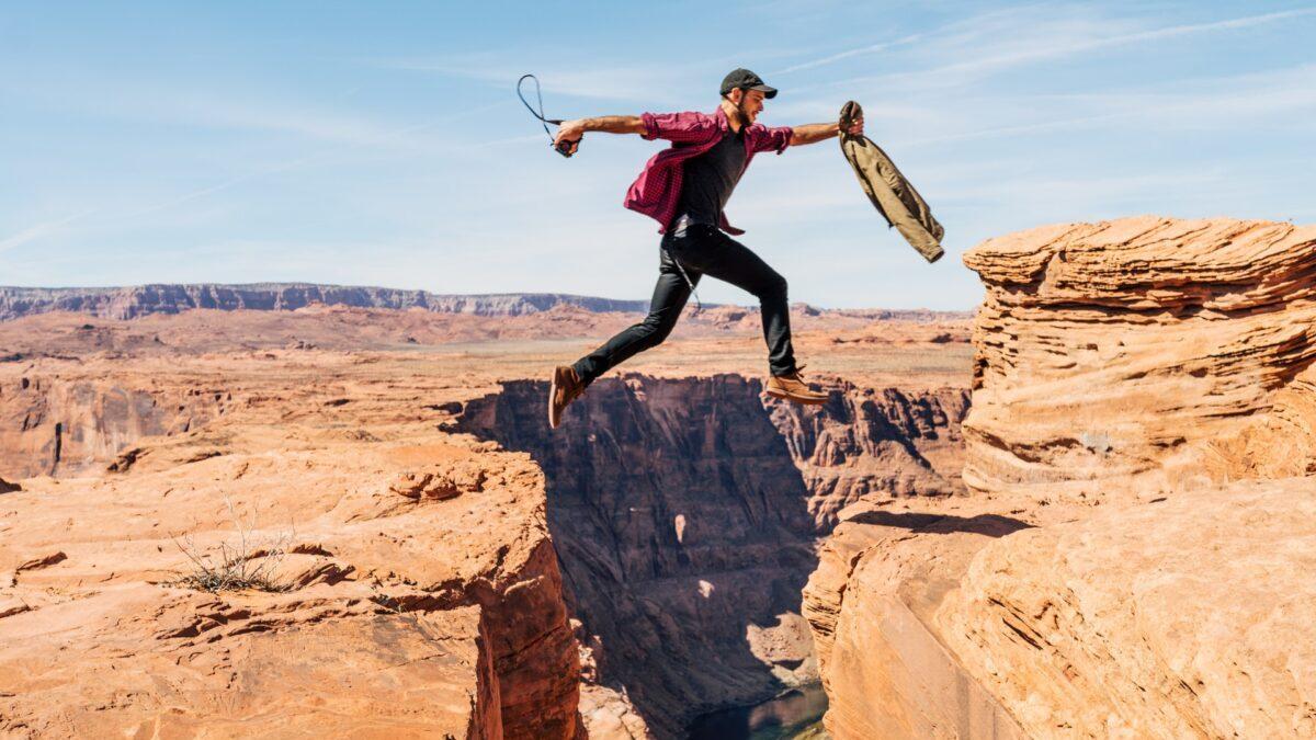 岩をジャンプする男性