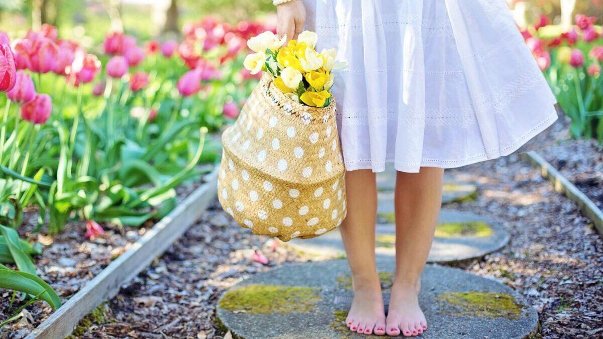 女性の足元と花